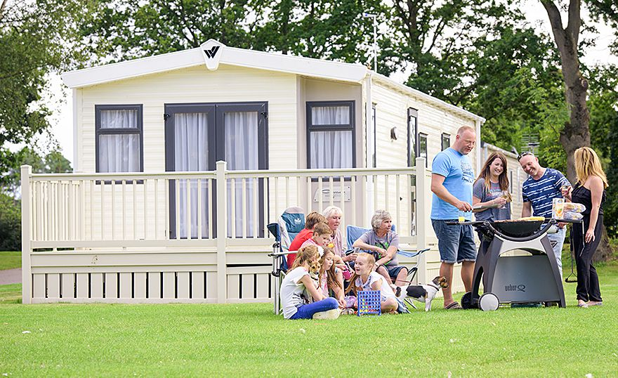 family outside static caravan holiday home